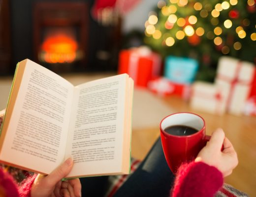 Woman reading a book and drinking coffee at christmas